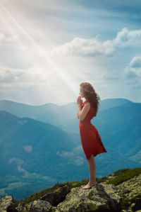 Beautiful woman praying in mountain landscape