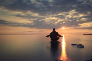 man meditates on the lake
