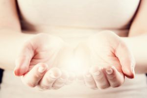 Light in woman hands. Giving, protect, care, energy concept.