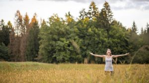 Young woman standing in the middle of autumn meadow with high go