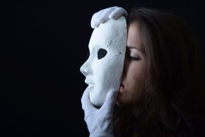 brunette girl holding a white theatrical mask